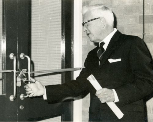 Sir Neville Barnes Wallis who in 1951 became Chairman of the first Board of Trustees.  He is shown here in 1966 cutting the ribbon at the opening of the new Hall